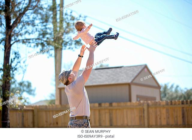 Young male soldier lifting up toddler daughter in garden at air force military base