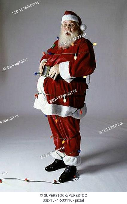 Portrait of Santa Claus with Christmas tree lights around him