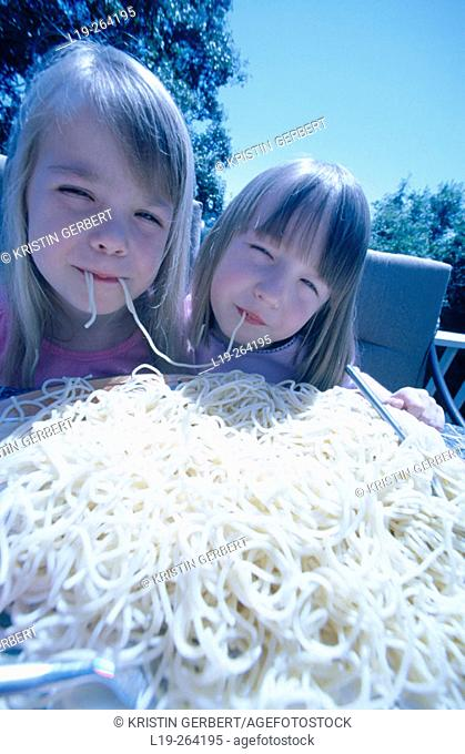 Twins eating a gigantic bowl of spaghetti
