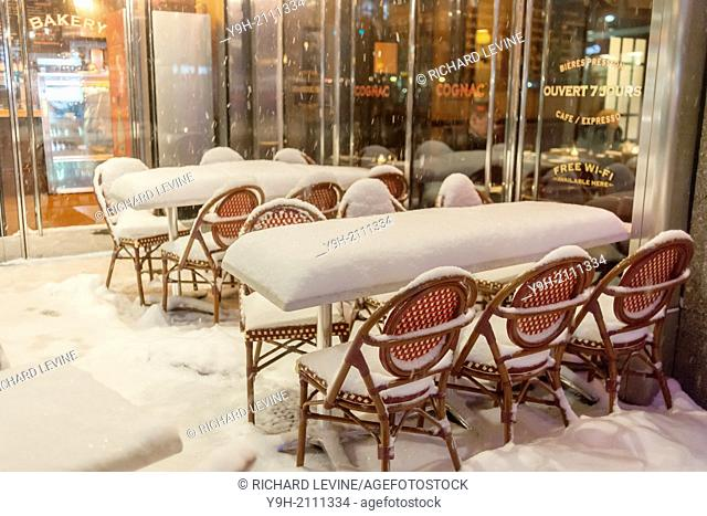 An empty snow covered outdoor cafe in New York during a snow storm
