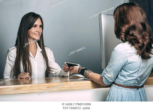 Young saleswoman handing repaired smart phone to female customer at counter