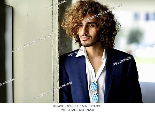 Portrait of stylish young man with beard and curly hair