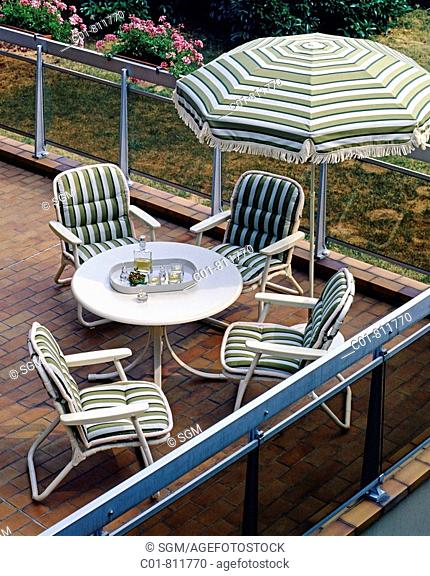 Garden furniture on a terrace, armchairs and parasol decorated with green