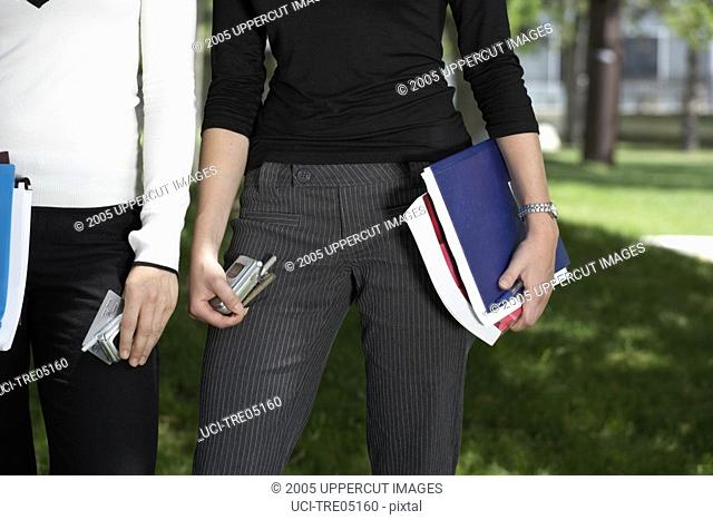 Woman holding books and cell phone in park