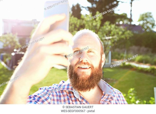 Young man with smartphone in garden, selfie