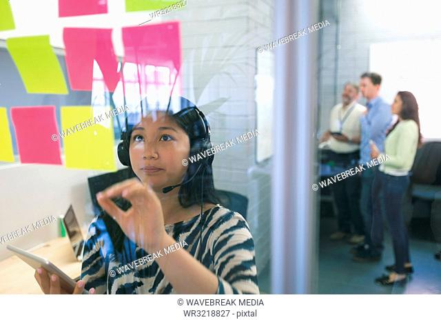 Female executive looking at sticky notes