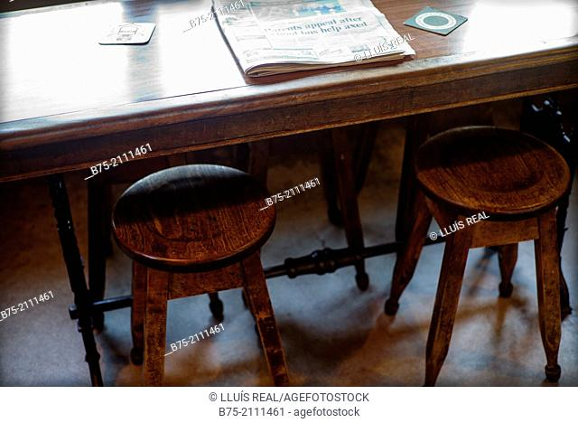 Pub table with two stools and a newspaper in Yorkshire Dales, England, UK, Europe
