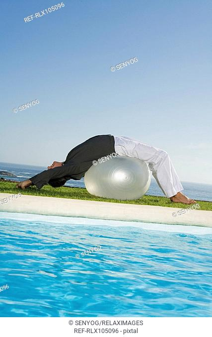 Mature man doing Pilates exercises with Gymnastic ball at poolside