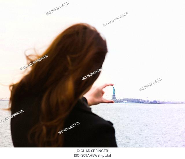 Young woman aligning fingers with statue of liberty, New York, USA