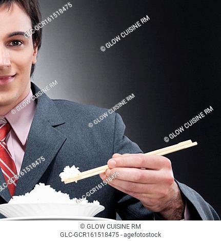 Businessman eating rice with chopsticks