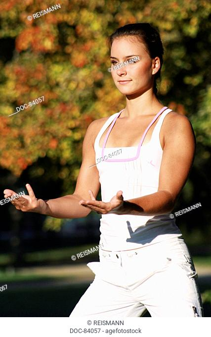 Young woman in an autumnal park practising a medical Qi Gong exercise - cardiac exercise and small intestine exercise
