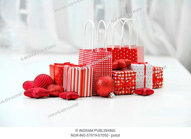 Gift boxes with xmas presents wrapped in red paper with ornament on light interior background