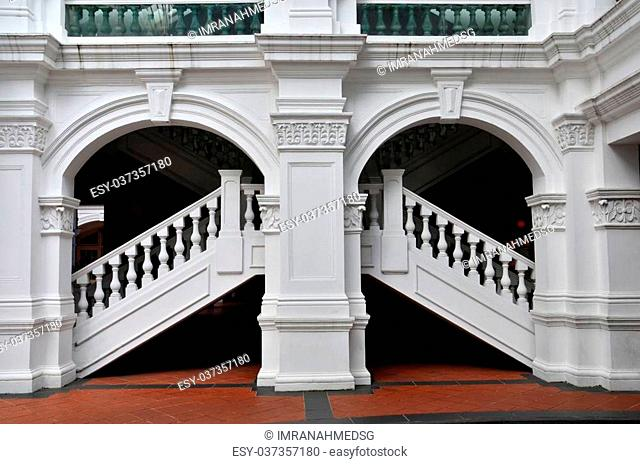 An artistically designed up and down white staircase with balustrade and columns by the kerbside