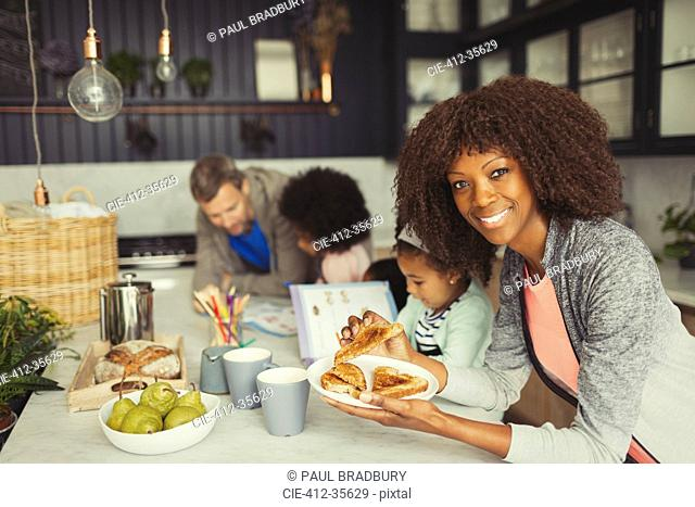 Portrait smiling mother eating breakfast toast with young family in kitchen