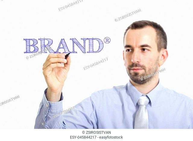 Brand (R) Young businessman writing blue text on transparent surface - horizontal image