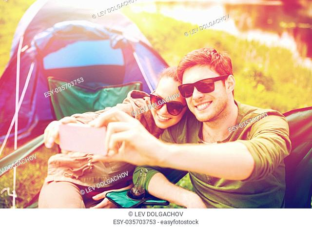 travel, hiking, technology, tourism and people concept - smiling couple of travelers taking selfie by smartphone at camping