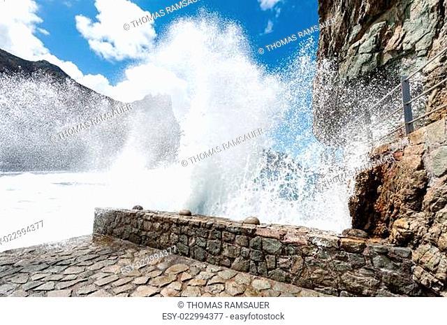 Welle bricht an Hafenmauer