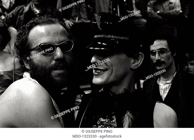 Two men dressed up. Two men dressed up embrace during a fancy dress party in Studio 54 disco. Milan, 1979