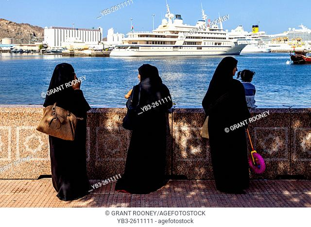 A Group Of Omani Women Look Out Over The Port At Muttrah, Muscat, Sultanate Of Oman