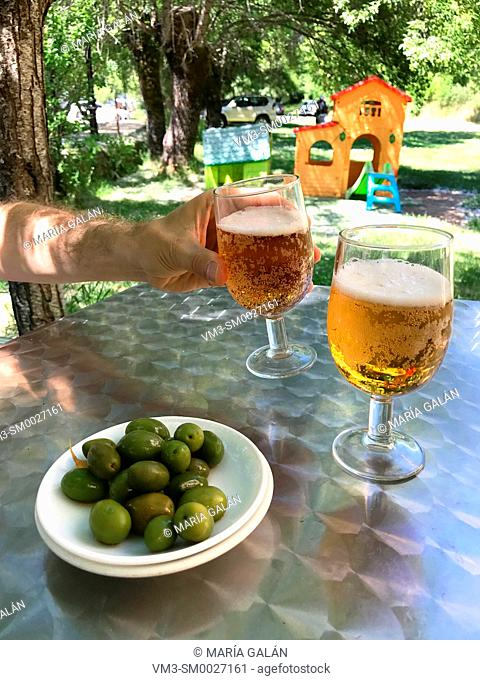 Two glasses of beer with green olives as tapa in a terrace. Spain