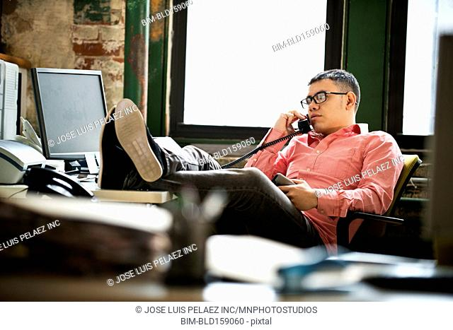Hispanic businessman talking on telephone at office desk