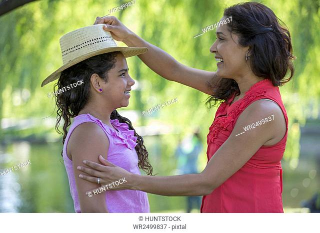 Hispanic mother fixing her daughter's hat in the park
