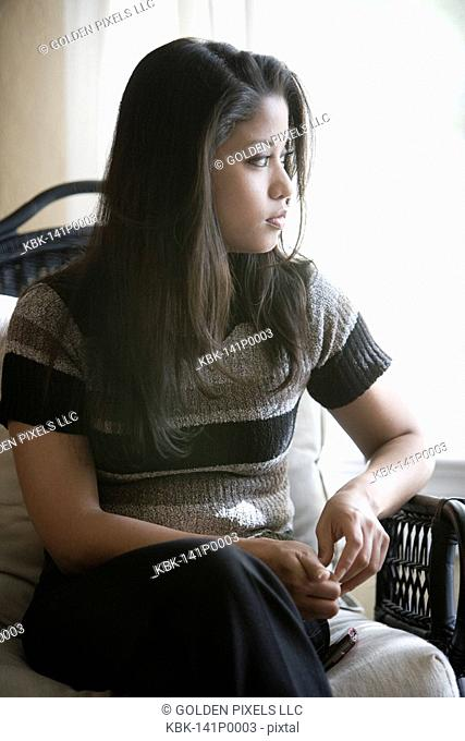 Young Asian woman sitting by window