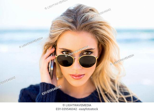 Serious gorgeous blonde on the phone looking over her sunglasses on a beautiful wild beach