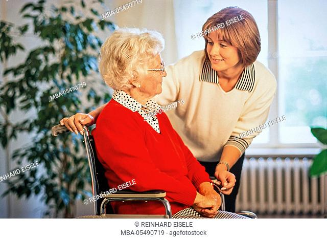 Young woman at the conversation close a senior who sits in a wheelchair