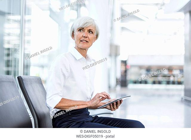 Senior businesswoman sitting in waiting area with tablet looking around