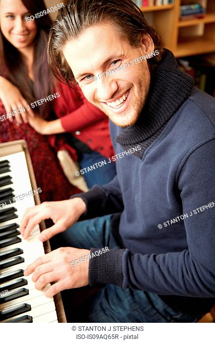 Portrait of young man playing the piano for girlfriend