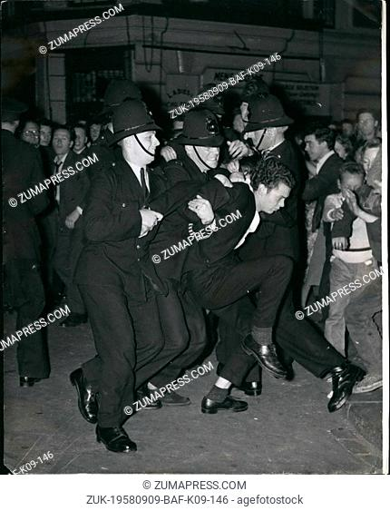 Sep. 09, 1958 - 'Colour' riots in Notting Hill gate a demonstrator is marched off: Police reinforcements were rushed to London's Notting Hill gate last night as...