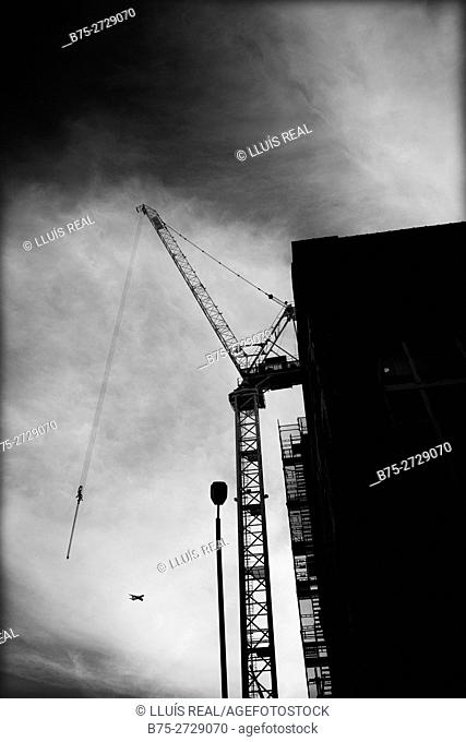 Silhouette of construction crane and building, with airplane in background. London, England