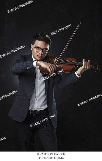 Confident musician playing violin while standing against black background