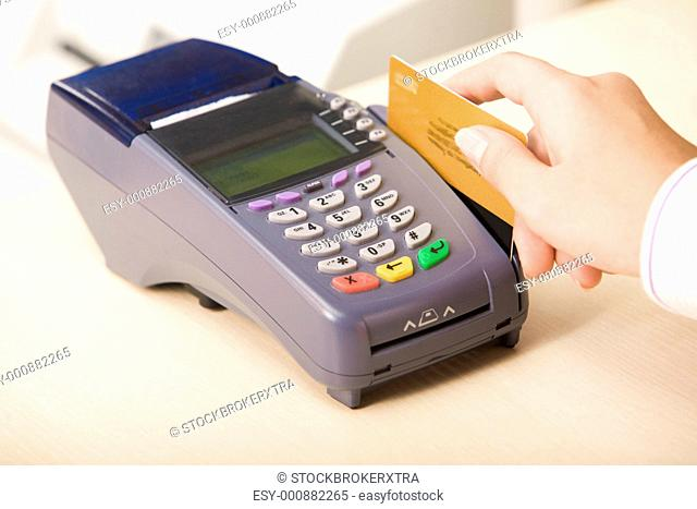 Photo of shop assistants hand with credit card during financial operation