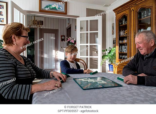 ELDERLY COUPLE PLAYING SCRABBLE WITH THEIR GRANDSON IN THE HOME, TOWN OF VERNEUIL-SUR-AVRE (27), FRANCE