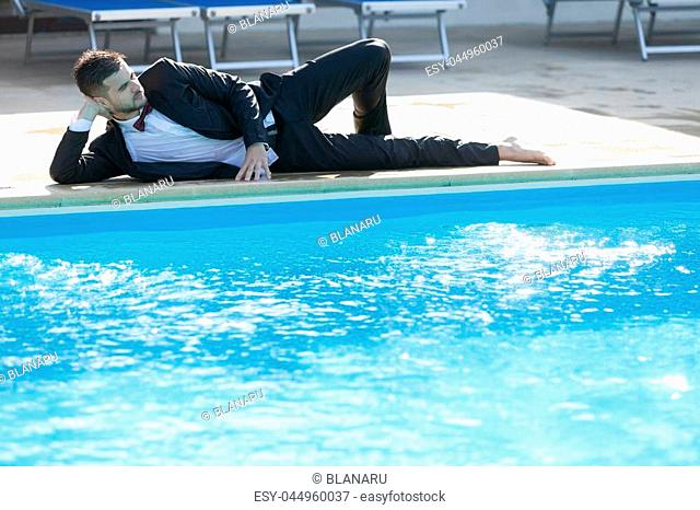 Man sitting by the pool, wearing black suit feeling sad and dissapointed