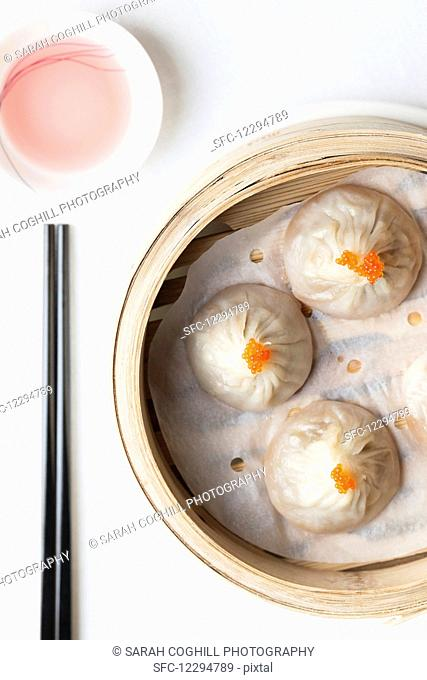 Steamed Chinese dumplings with fish roe in bamboo steaming basket with chopsticks and dipping sauce