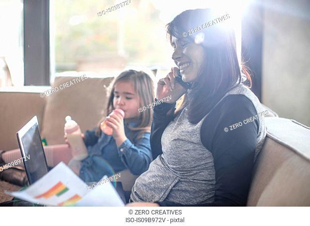 Girl with baby bottle while mother working on sofa making smartphone call