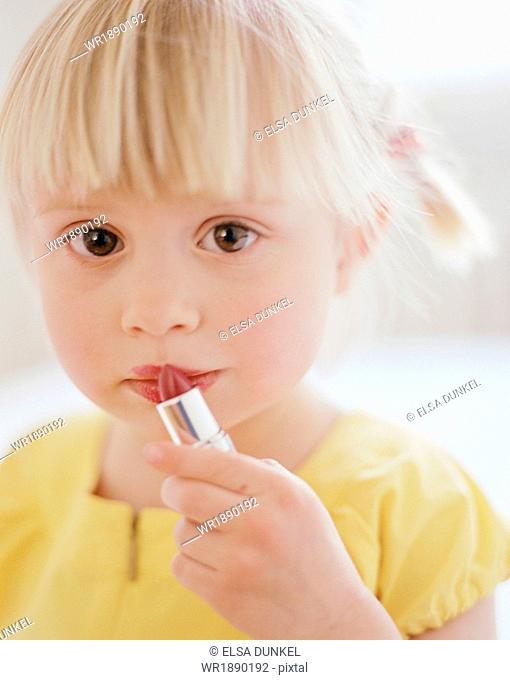 Little Girl Putting On Lipstick, Munich, Bavaria, Germany