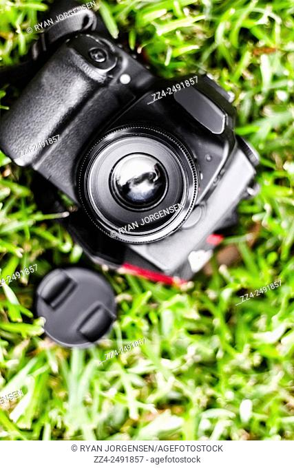 Closeup view of digital SLR camera sitting on a green grassy field with 50mm lens. Artistic still-life objects