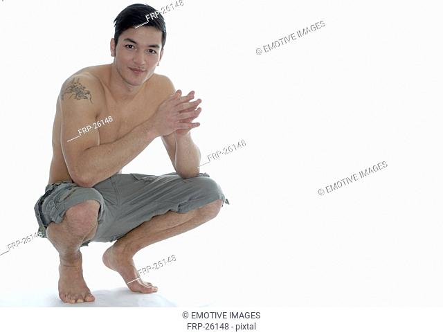 Young man with tatoos on his arm sits on his haunches