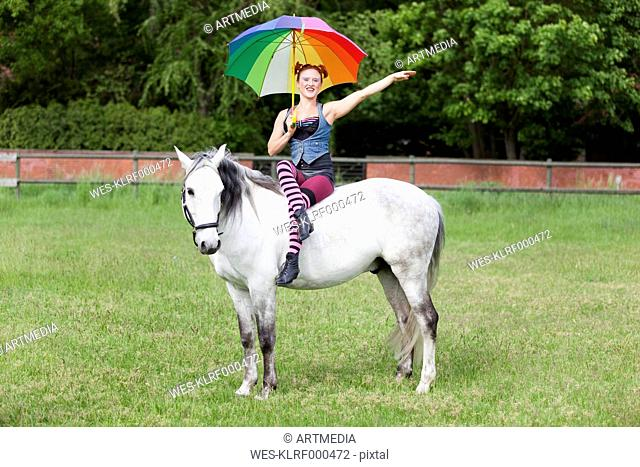 Woman sitting with umbrella on white horse