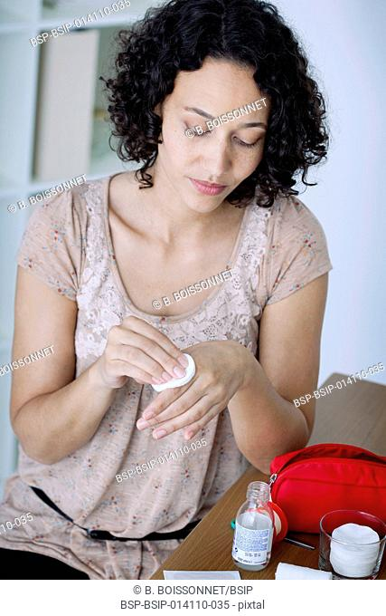 Woman disinfecting a wound