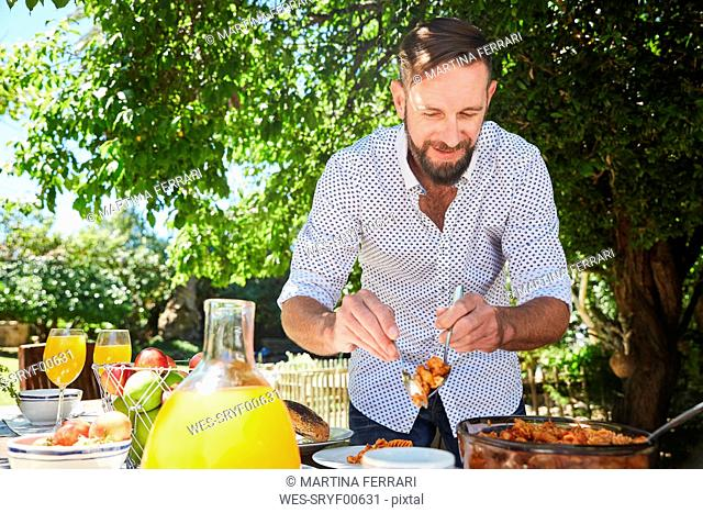 Man dishing up pasta at garden table
