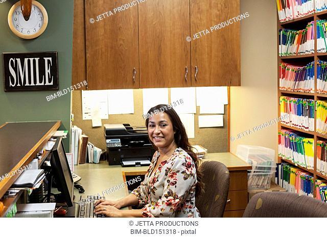 Hispanic medical receptionist smiling behind desk