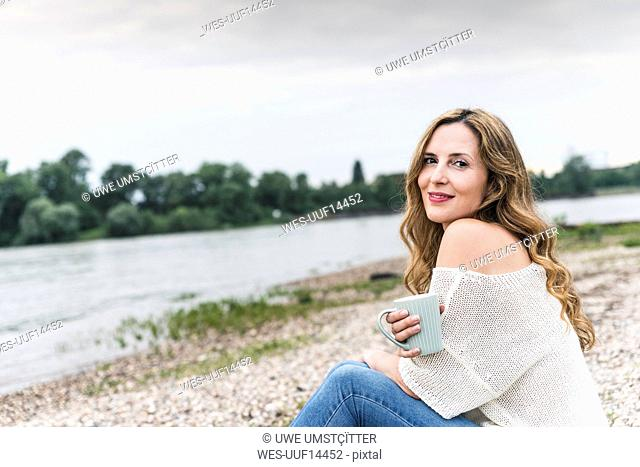 Smiling woman with cup of coffee sitting at the riverside