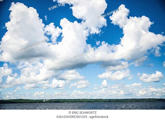 Fluffy White Clouds in Blue Sky Above Lake