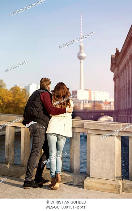 Germany, Berlin, young couple at River Spree looking at TV tower