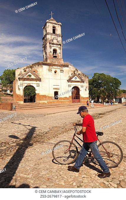 Cyclist infront of the Santa Ana church, Trinidad, Sancti Spiritu Province, Cuba, West Indies, Central America